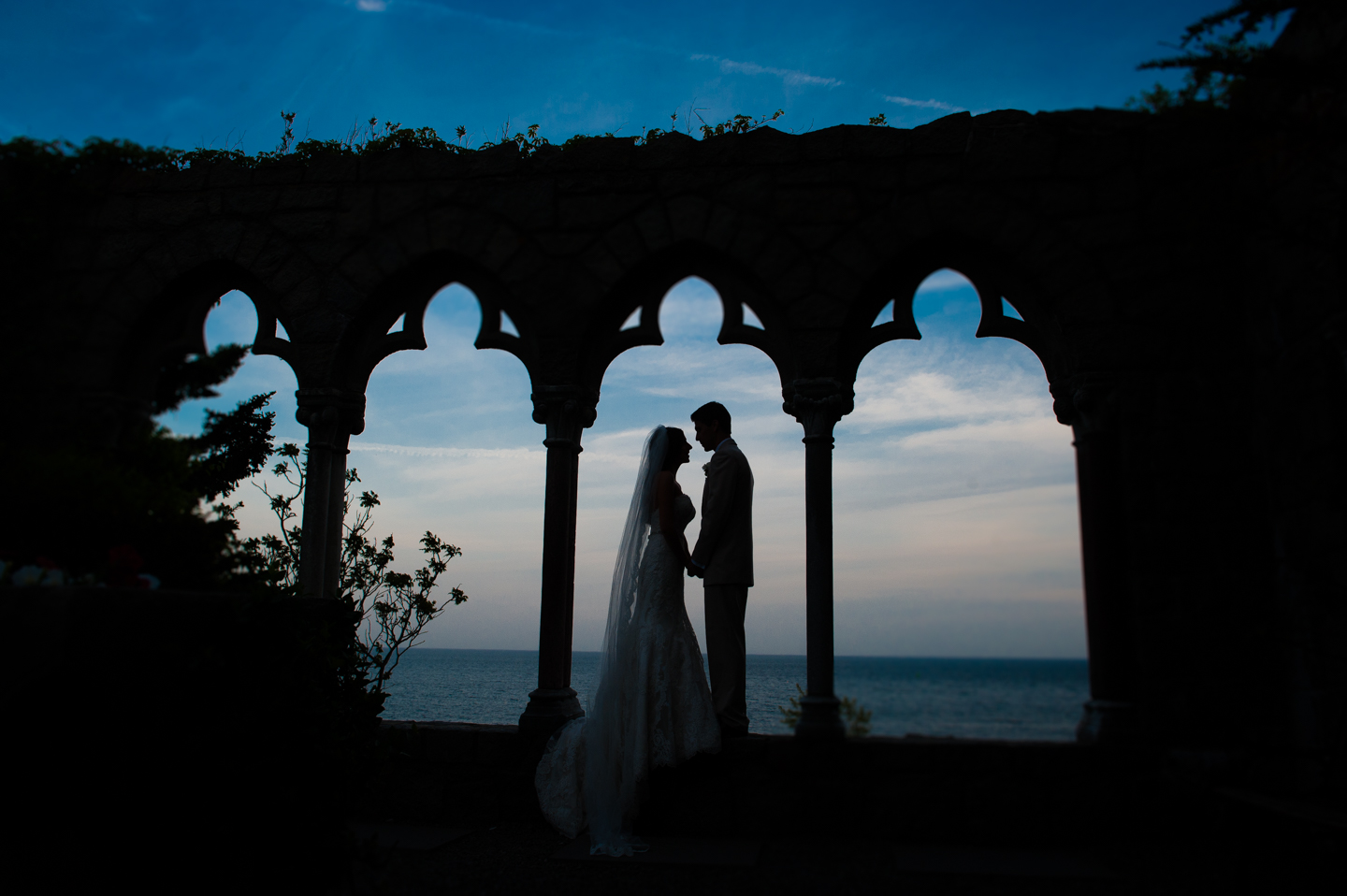 Silhouette of couple in castle arches by the ocean during their wedding