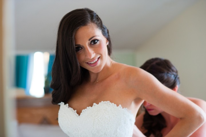 beautiful brides gets zipped into her wedding gown