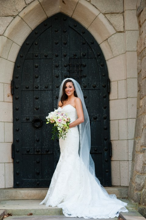Beautiful bride with her bouquet poses on castle drawbridge