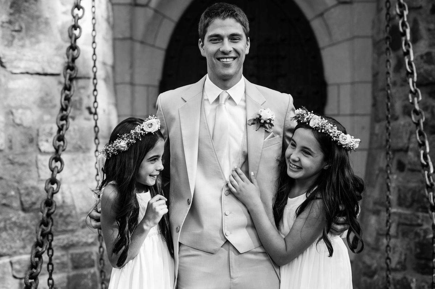 two adorable flower girls pose laughing with the groom