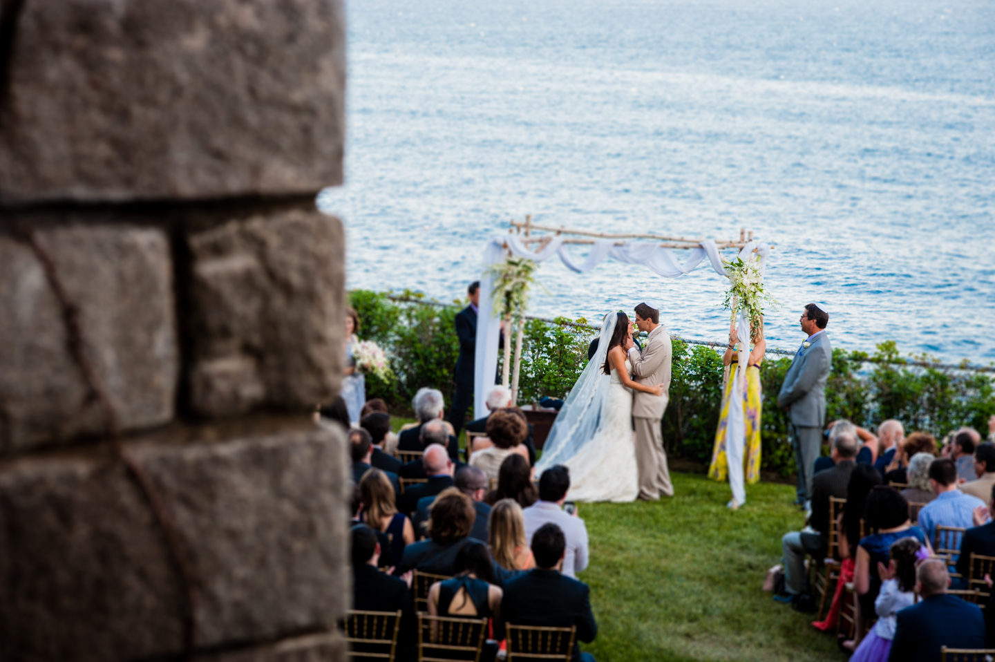 bride and grooms first kiss as husband and wife after their seaside wedding ceremony