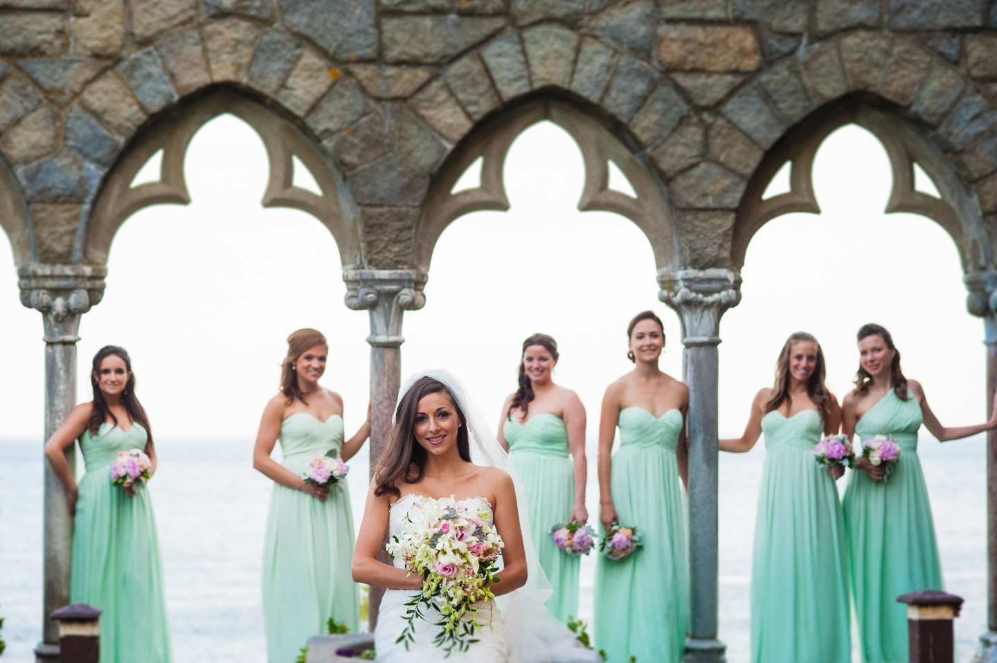 Beautiful bride and her bridesmaids pose for a portrait  by some stone arches at Hammond Castle