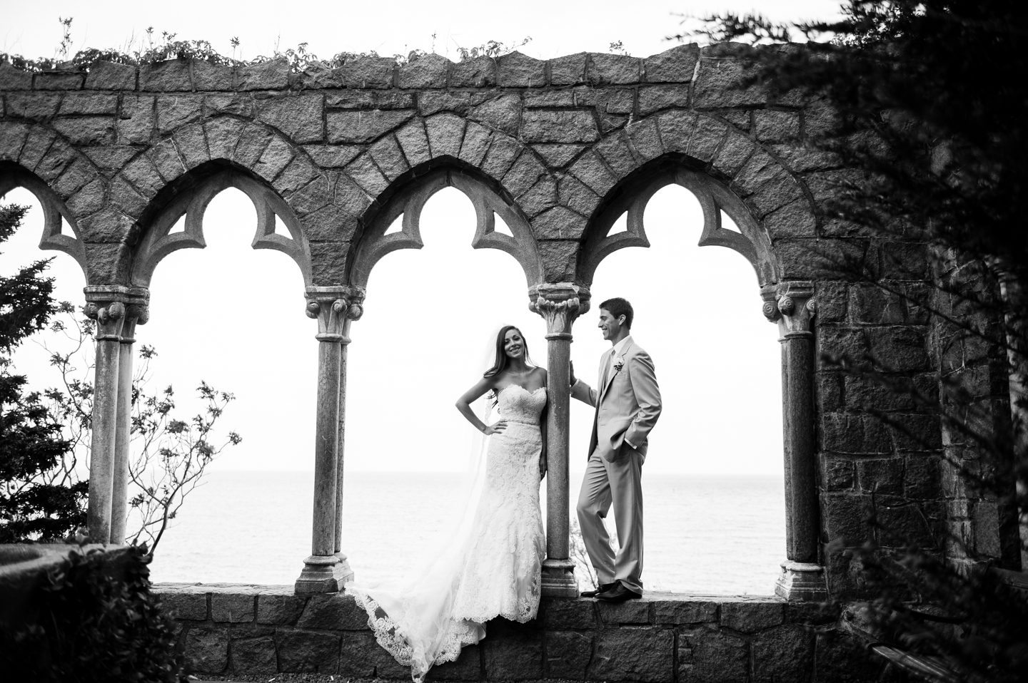 black and white image of bride and groom by the arches at Hammond Castle