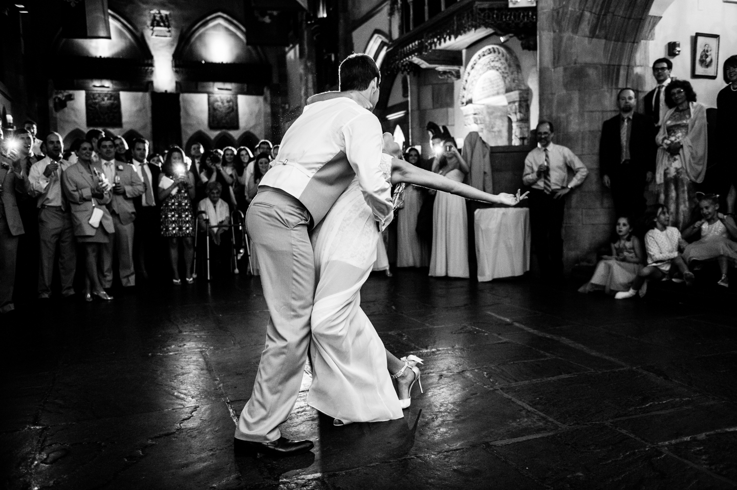 groom dips his bride during their fun first dance