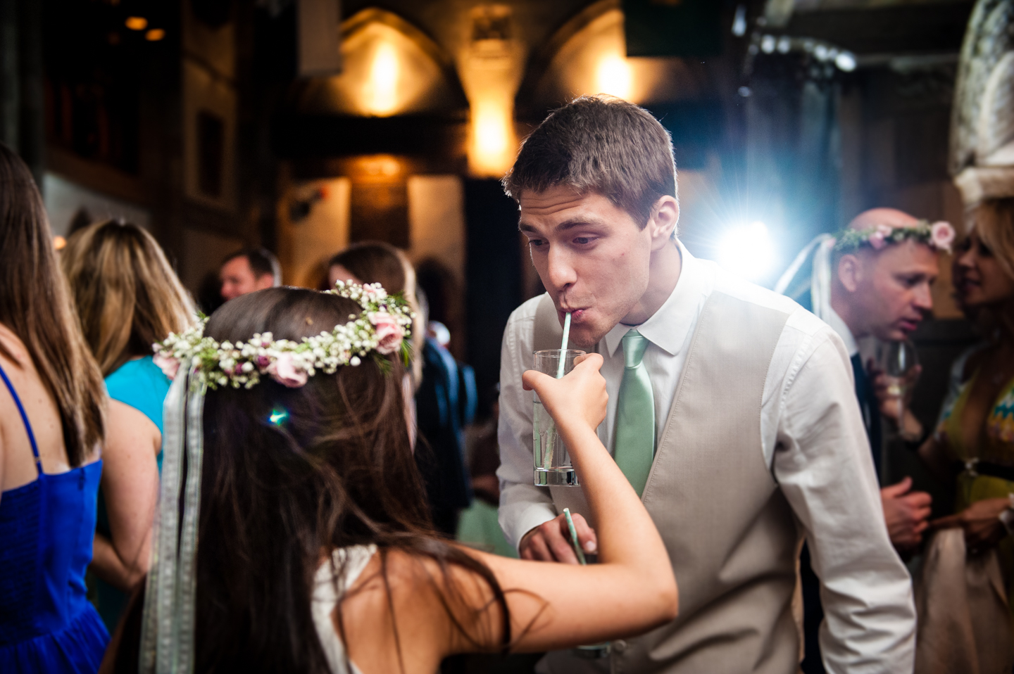 flower girl shares her drink with the groom during wedding reception