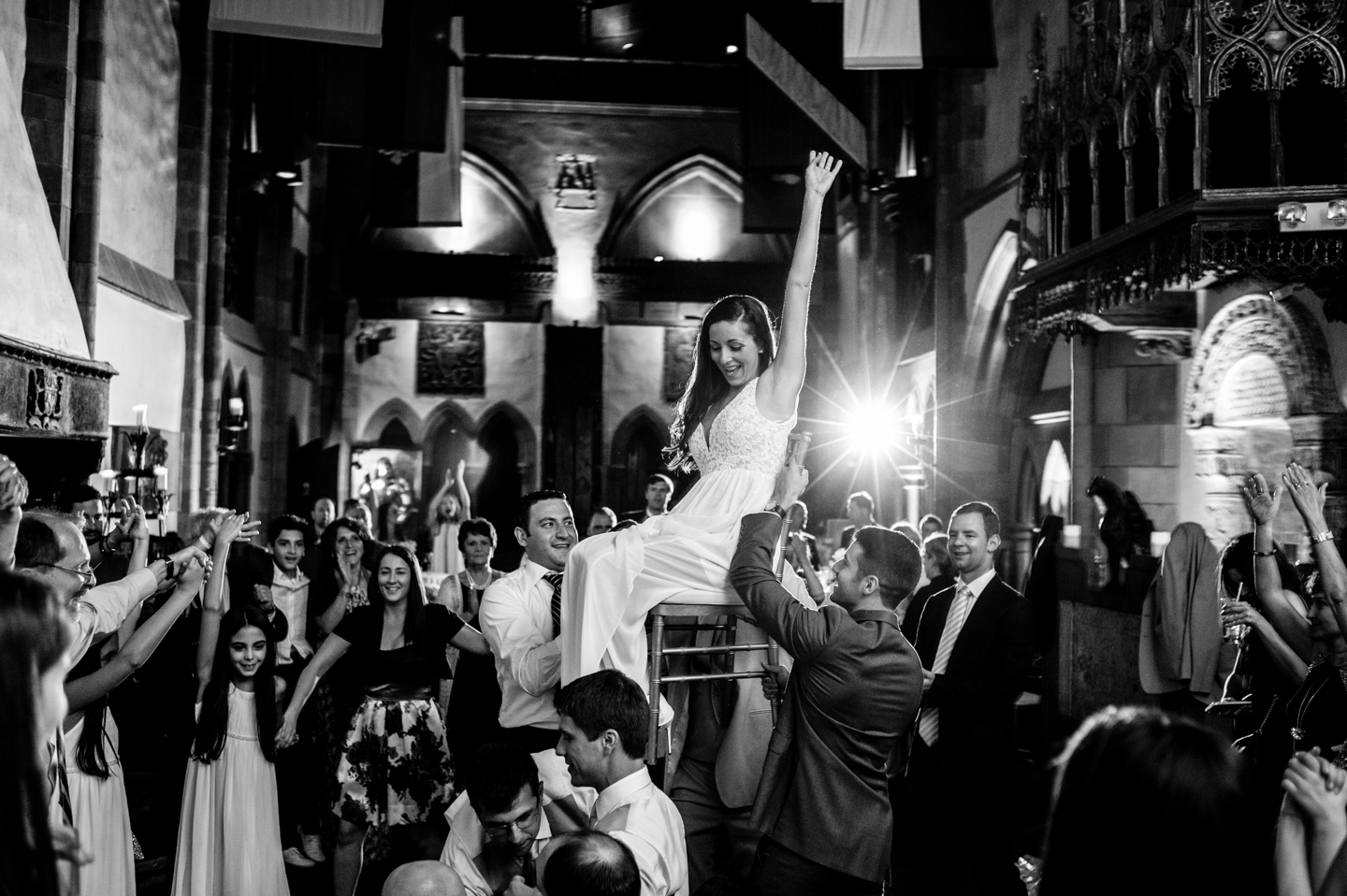 Bride lifted up in chair during the Hora