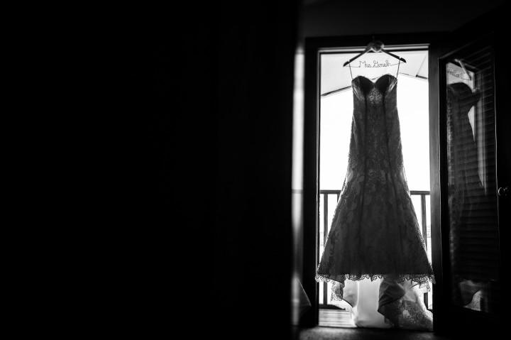 wedding dress hangs  silhouetted in doorway in black and white