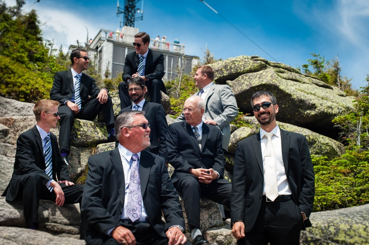 Groom and groomsmen hike in suits for a pre wedding portrait session with amazing views