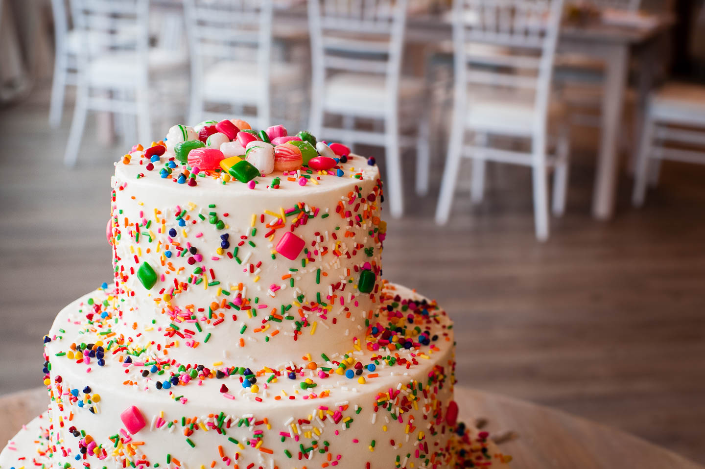 An amazing wedding cake covered in white frosting, sprinkles and chicklets