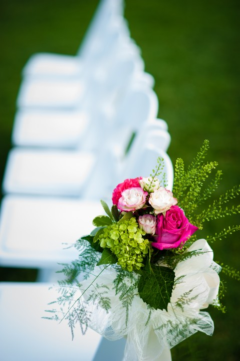 Beautiful pink and green flowers adorn the white ceremony chairs during this beautiful barn wedding
