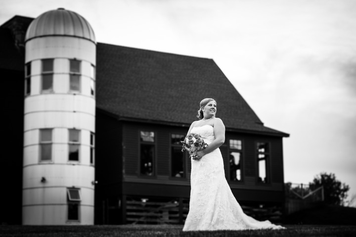 Bride poses for a quick bridal portrait in front of a barn and silo