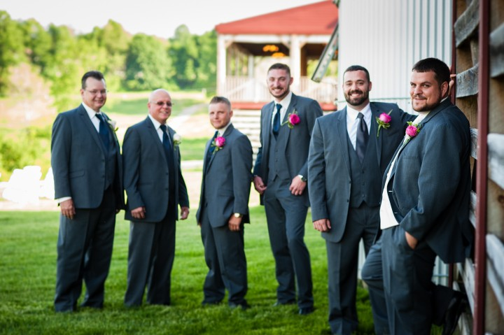 The handsome groom and his groomsmen pose against a barn before his wedding ceremony