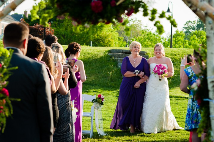 Bride and her mom walk down the aisle of her rustic farm wedding ceremony