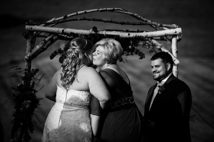 Bride and her mom embrace before mom gives her daughter away to groom before the couple gets married
