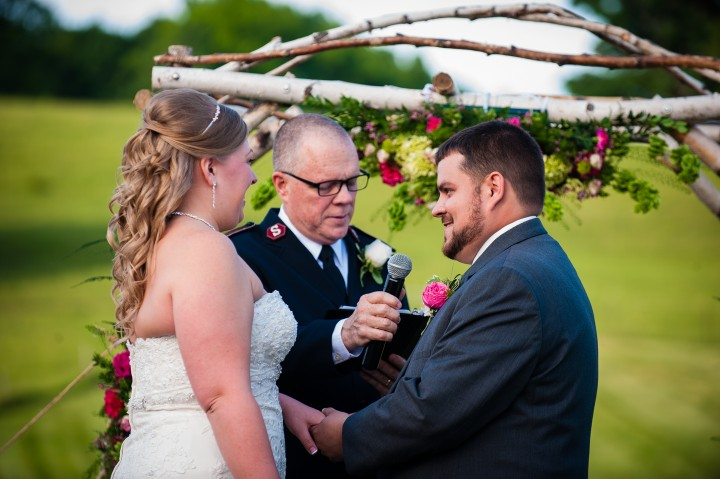 The bride and groom exchange wedding rings during their elegant wedding ceremony in a field