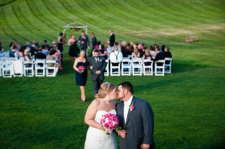 a gorgeous bride and groom kiss after their farm wedding ceremony