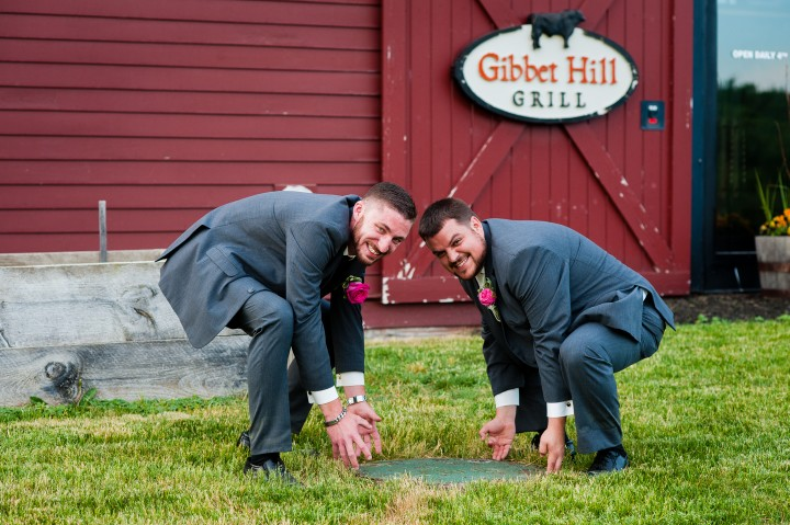 The groom and his best man goof off for a portrait in front of the Barn at Gibbet Hill