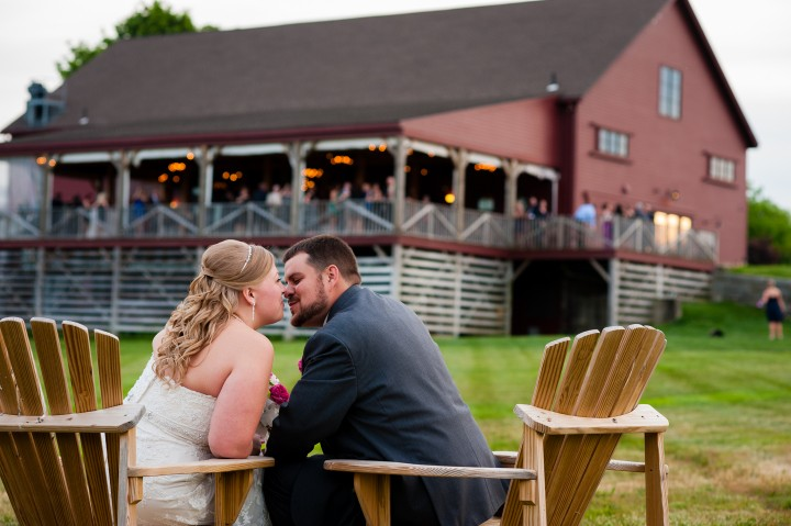 adorable bride and groom sit together in rustic adirondack chairs during their barn wedding