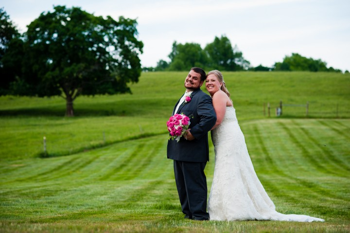 Bride and groom pose for a quick portrait together in a field after their wedding at the Barn at Gibbet Hill