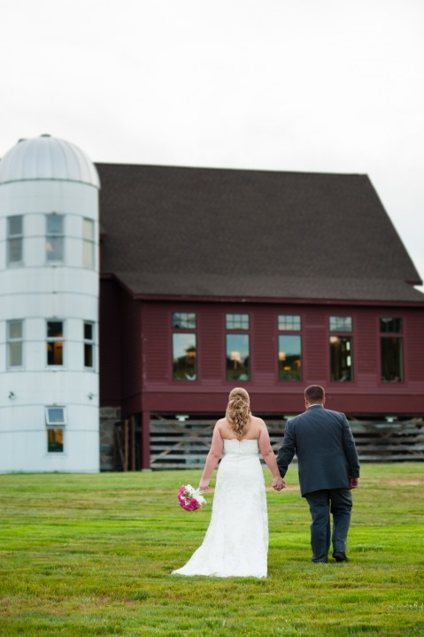 Bride and groom hold hands and walk across a field