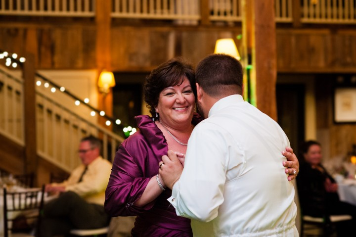 Groom and his mom dance during his barn wedding