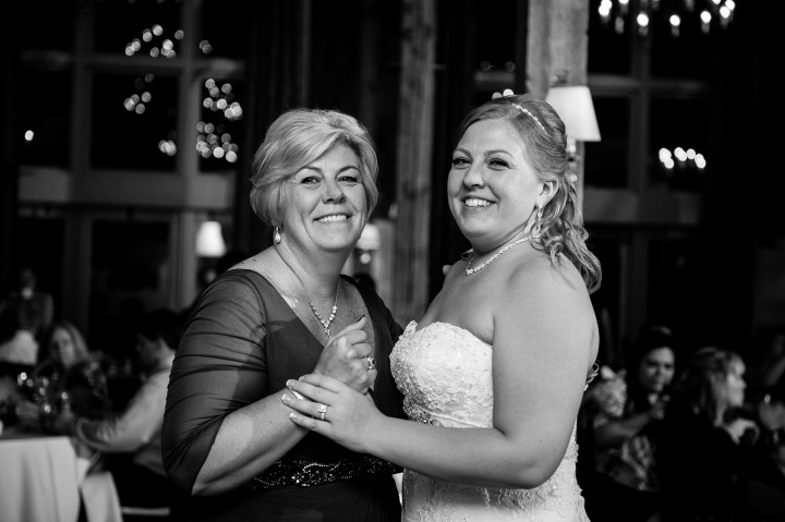 Bride and mom dance together during her barn wedding reception