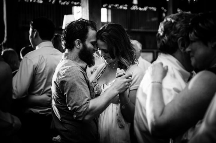 A cute couple dances during fun barn wedding