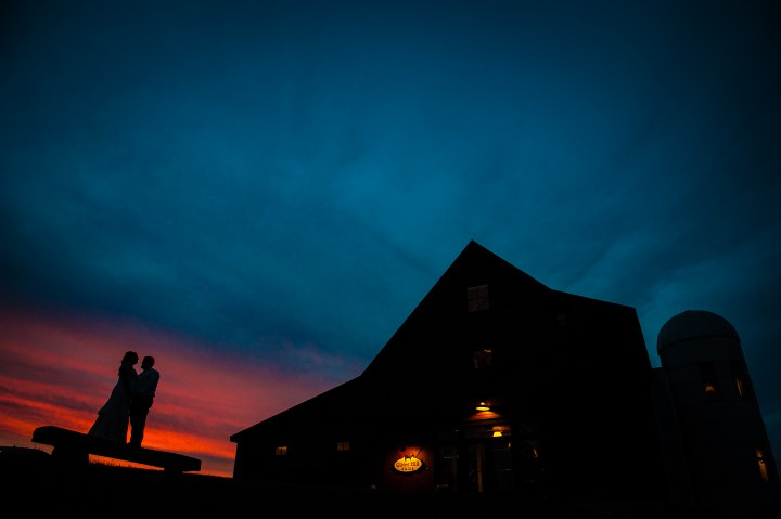 Silhouette of bride and groom at sunset with the barn at gibbet hill in the background