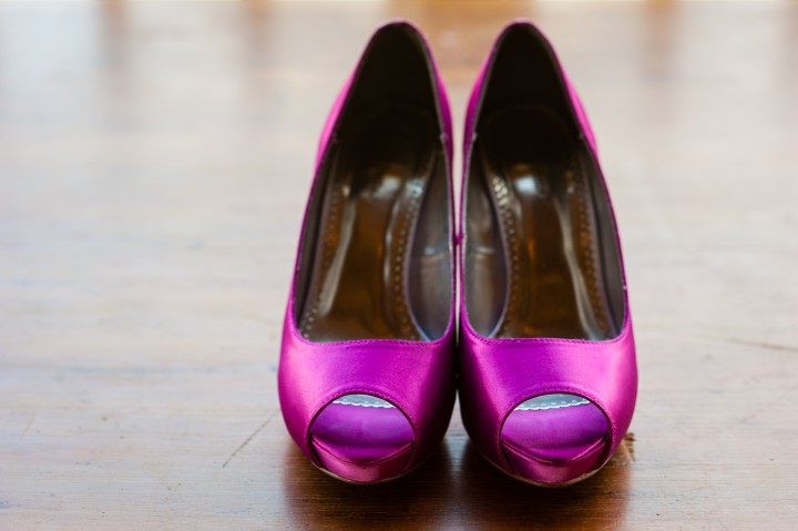 The brides pink shoes against a wooden chest