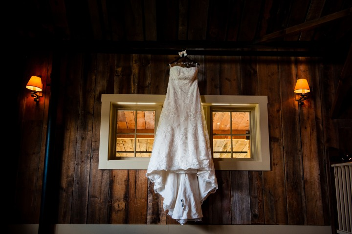Brides lace wedding dress hanging in a barn window