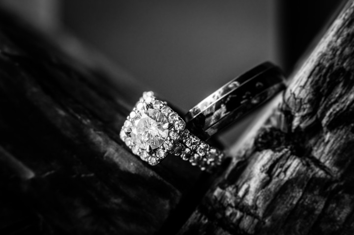 Black and white image of wedding rings on a wooden post