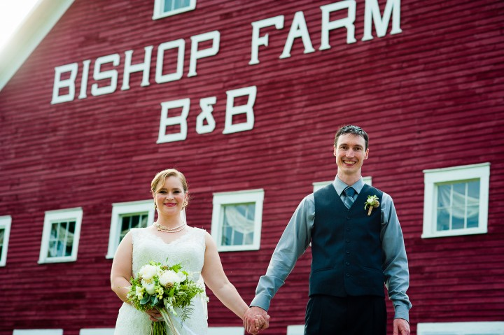 Bride and Groom pose in front of red barn during their rustic wedding at Bishop Farm
