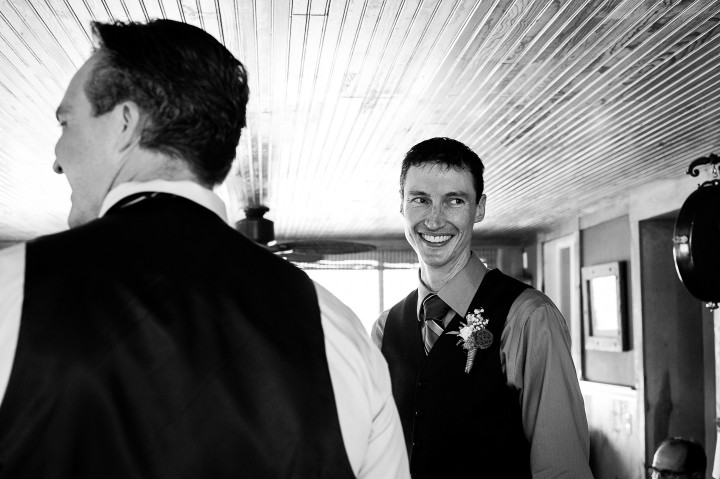 handsome groom gets ready in an old farmhouse before he gets married