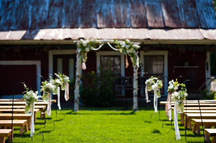 beautiful white flowers in mason jars line the aisle of this elegant outdoor ceremony