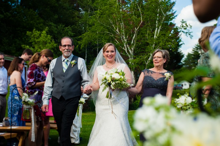 bride and her parents smile at guests while they walk down the aisle of an outdoor ceremony