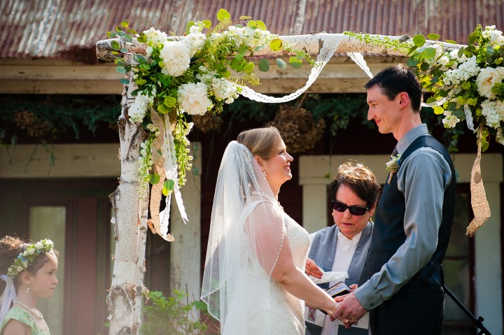 Bride and groom hold hands in from of birch arbor during their barn wedding ceremony