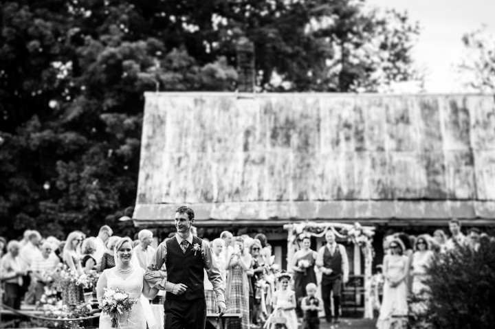 Bride and groom walk down the aisle after their barn wedding ceremony