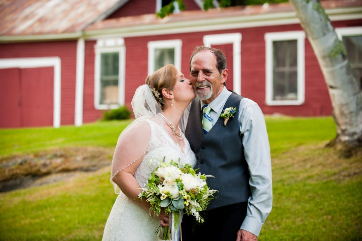 Bride gives her dad a quick kiss on the cheek during pictures at her farm wedding