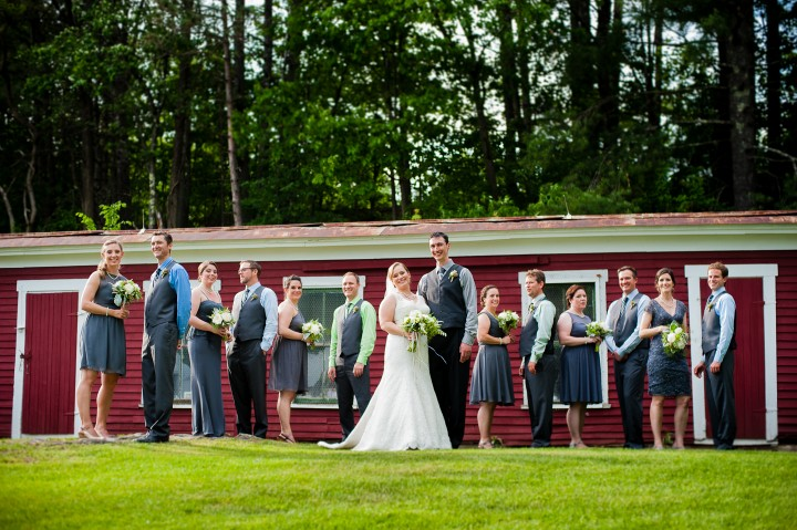 beautiful wedding party poses in front of a red barn for a quick group photo