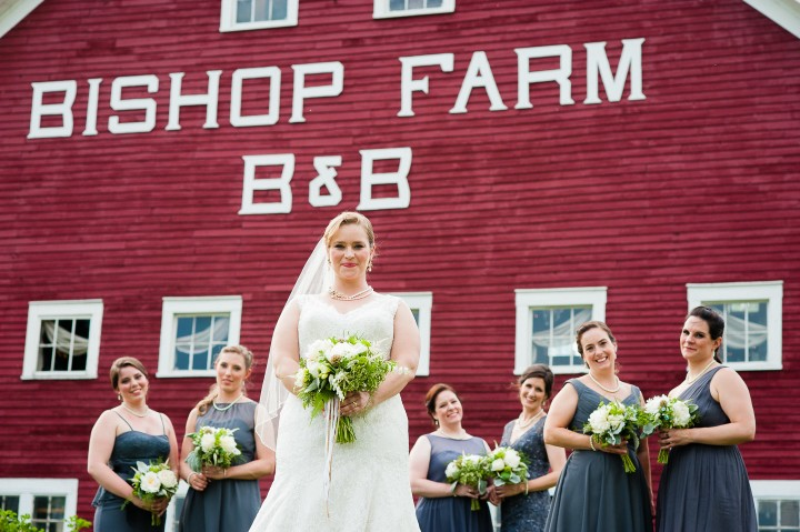 bride and her beautiful bridesmaids pose in front of big red barn