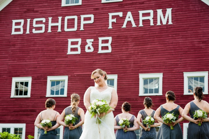 bride smiles at the camera while her bridesmaids show off their beautiful bouquets