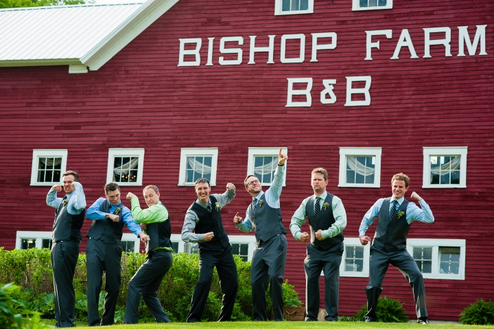 The handsome groom and his groomsmen goof off for a picture at their barn wedding