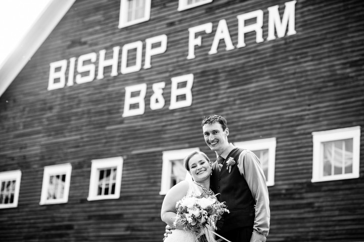 Bride and groom pose smiling at the camera during their barn wedding reception