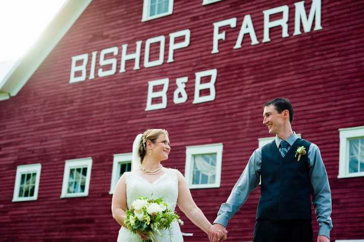 bride and groom hold hands and look at each other in front of red barn