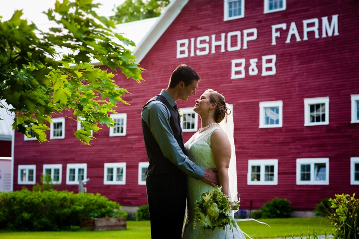 bride and groom embrace in front of beautiful red barn during their farm wedding