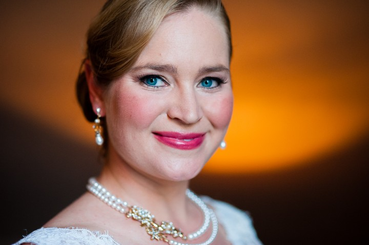 Stunningly beautiful bride with blue eyes and classic pearl jewelry poses for a quick bridal portrait