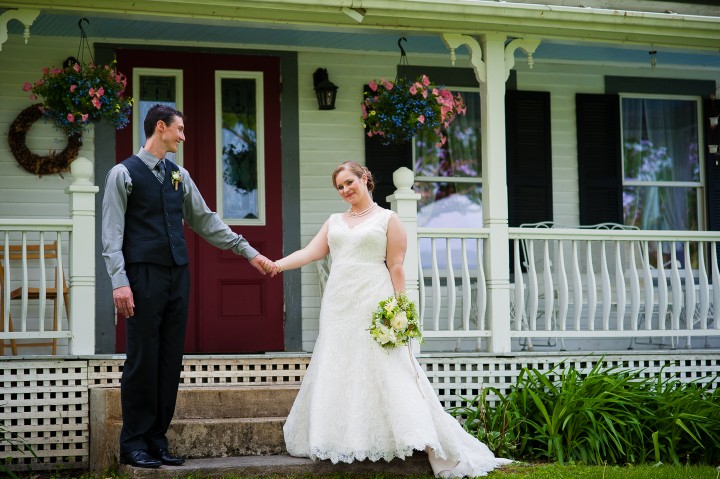 bride and groom hold hands in front of gorgeous old farmhouse