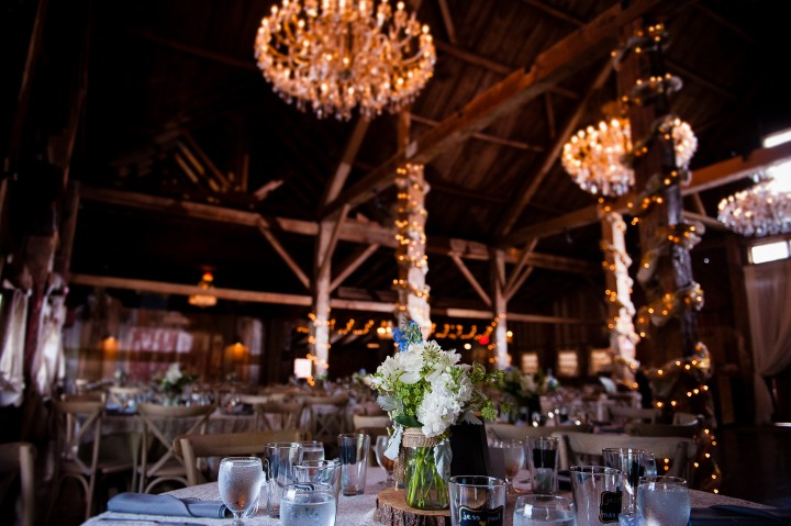 Beautiful purple and green flower centerpieces complimented the rustic wood interior of this barn wedding