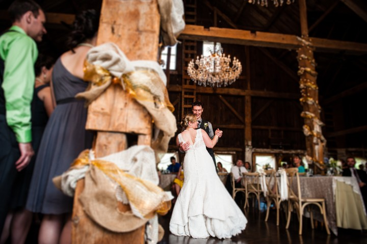 beautiful bride and groom enjoy their first dance in an elegant barn