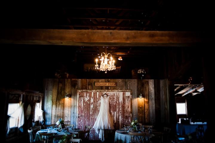 The brides lace wedding gown hangs in a barn for a pre-dressing image